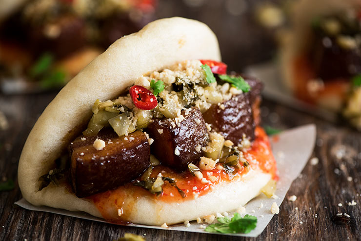 Melt in the mouth savory pork belly stuffed in soft, fluffy mantou with sweet & spicy chili sauce and crunchy sour pickled mustard greens.
