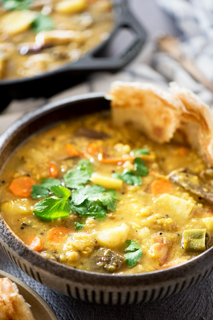 Flavor packed hearty & healthy South Indian lentil based curry stew filled with vegetables. It's mildly spicy and a tad sour from the tamarind & tomatoes.