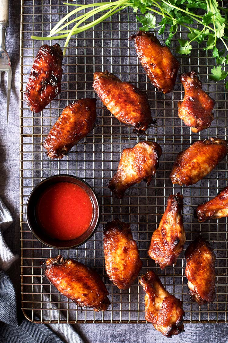 Smoky savory BBQ chicken wings with a tangy spicy chili sauce. Grilled or roasted in the oven, these wing-asm in your mouth wings are perfect for summer.